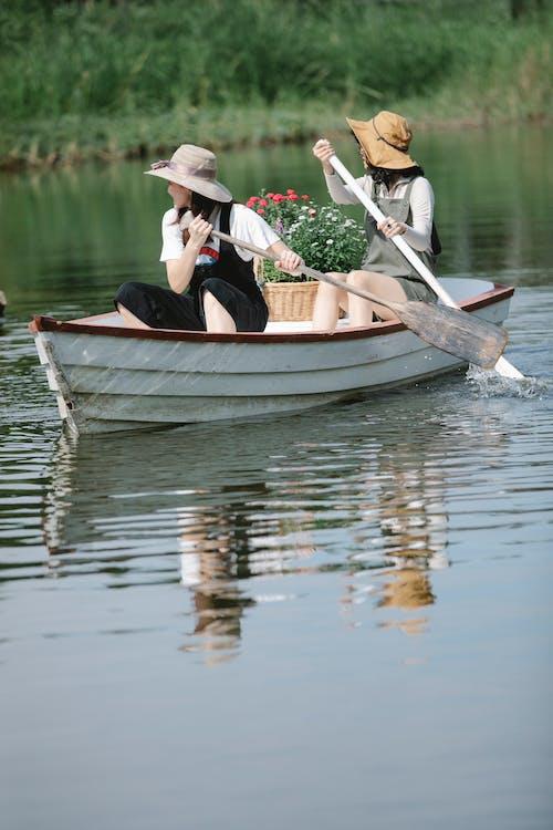 Faceless female friends floating on boat in lake near shore