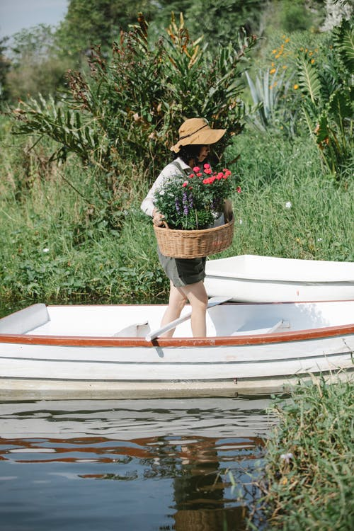 Side view of anonymous female gardener in overall and hat with wicker basket with flowers in boat near riverside with green grass and plants in sunny summer day in countryside