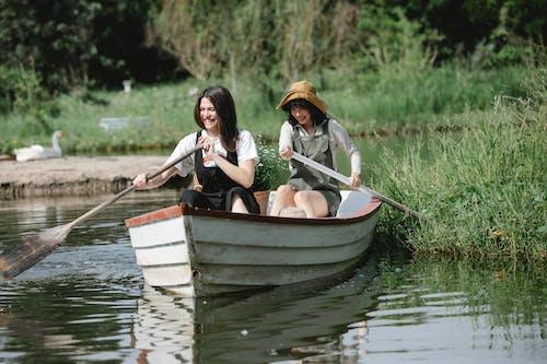 Happy women floating on boat in river near grassy coast