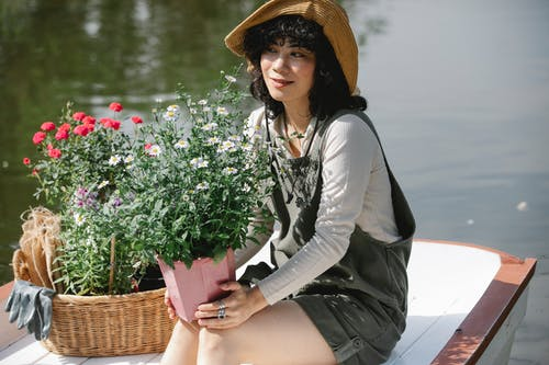 Asian woman with potted flowers sitting in boat in pond
