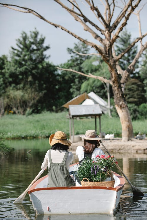 Back view of unrecognizable female friends in casual clothes and hats boating on calm lake in sunny summer day