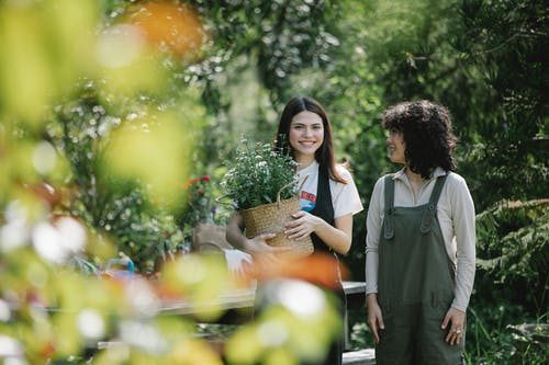 Young smiling female friends in casual clothes with basket of fresh flowers walking together in garden