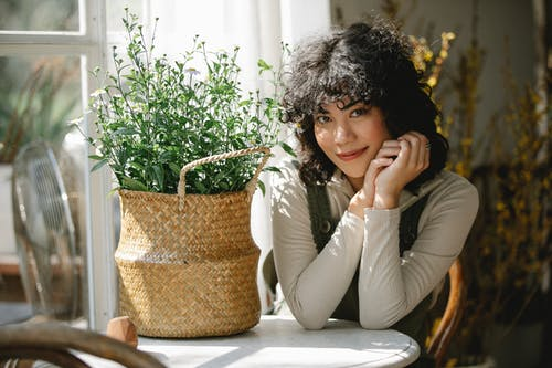 Young smiling Hispanic female in casual clothes sitting at table with basket of flowers and looking at camera