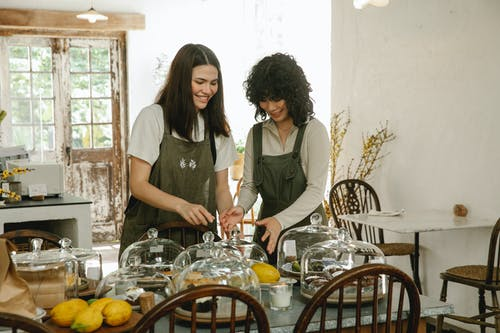 Positive young multiethnic waitresses in green aprons standing near table with assorted fresh desserts under glass domes preparing for tea time in cafe