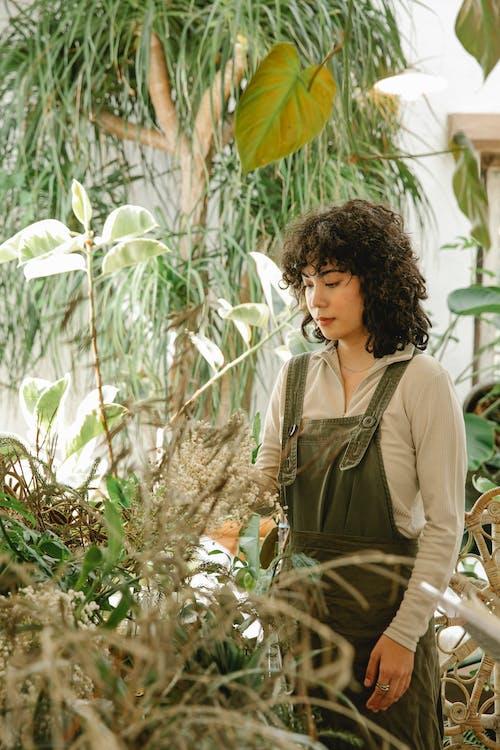 Femme En Veste Verte Debout Près De Plantes Vertes