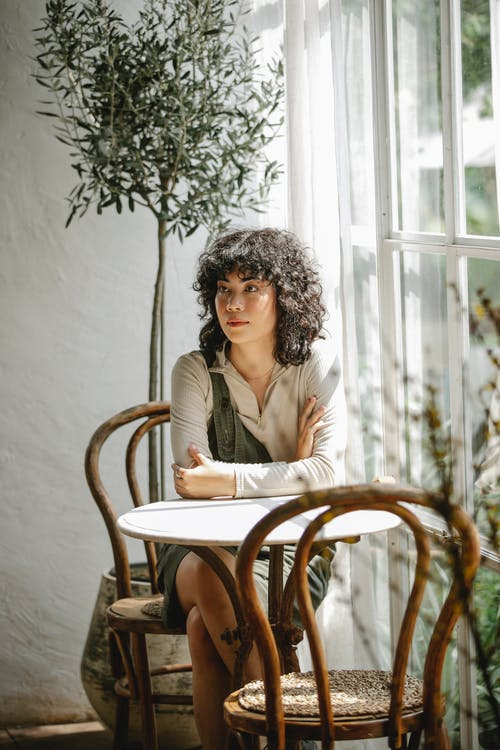 Charming woman sitting at table near window in cafe
