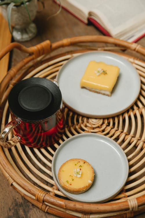From above of hot tea in teapot and tasty cheesecakes on plates placed on round wicker tray in cafe