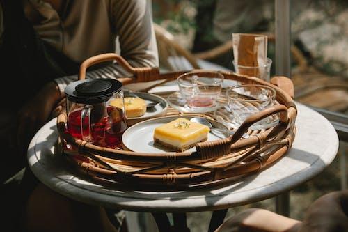 Persona In Camicia A Maniche Lunghe Grigia Che Si Siede Sulla Sedia Davanti Al Tavolo Con Gli Alimenti
