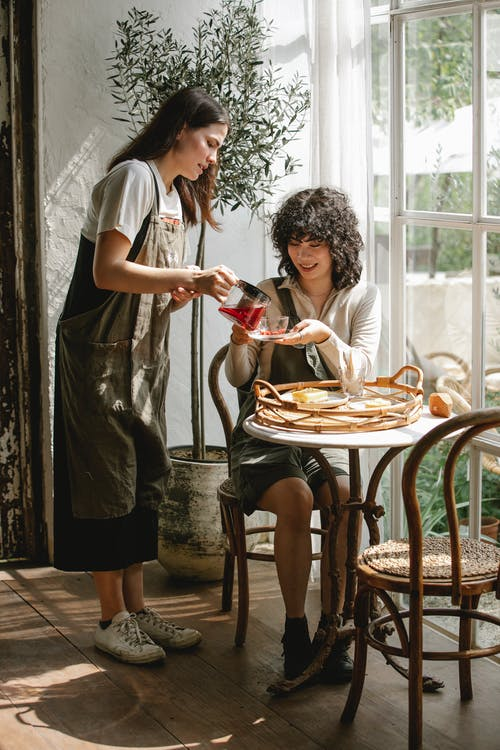 Woman pouring brewed tea into glass teacup to ethnic friend