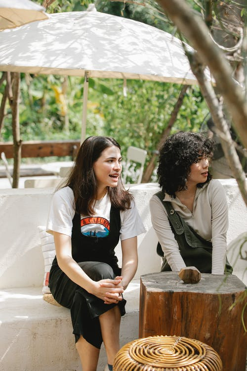 Young multiethnic women sitting on stone bench and having conversation and attentively looking away
