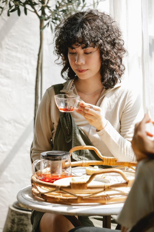 Curly haired female with glass cup of herbal tea sitting at table with friend