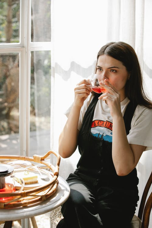 Serious female drinking tea sitting at table with breakfast near window and looking away