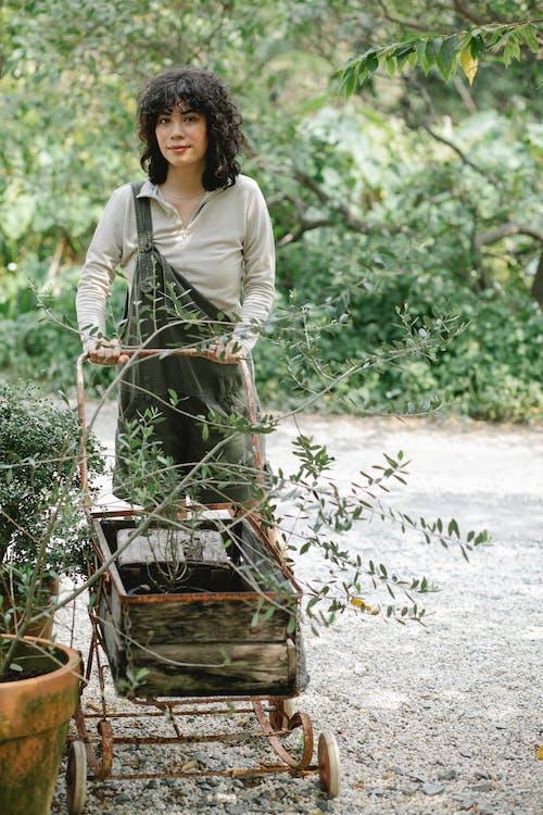 Ethnic female gardener rolling wooden cart in garden with plants in clay pots