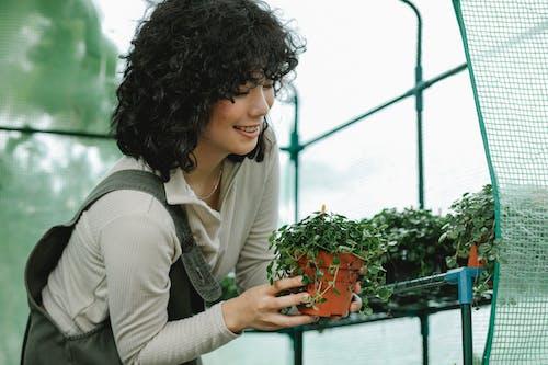 Femme En Cardigan Blanc Tenant Des Fleurs Orange