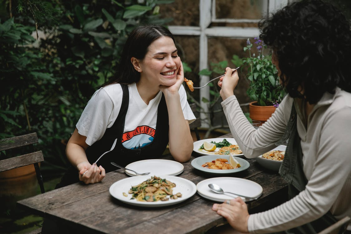 Female giving food on fork to cheerful friend while having lunch in outdoor terrace