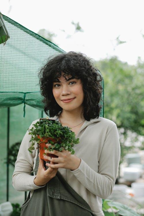 Smiling ethnic gardener with seedling in pot