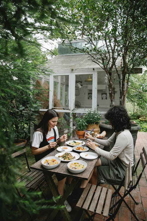 High angle of female farmers having lunch with different dishes in garden among green plants