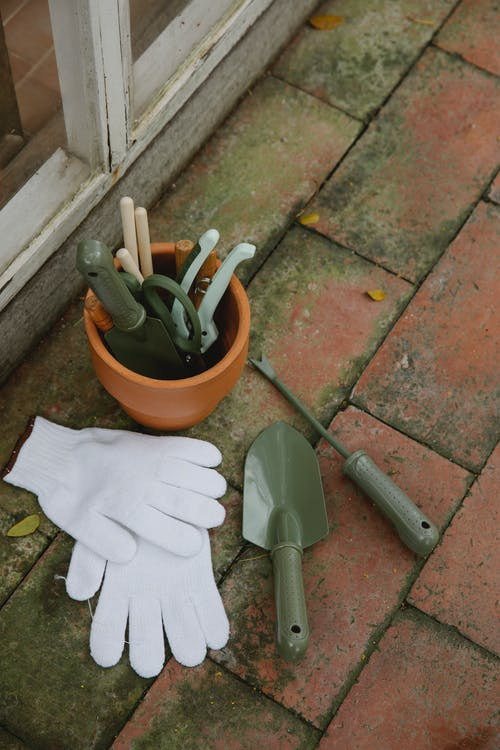 From above of various gardening instruments including shovel hoe pruner placed on tilled floor near pair of gloves