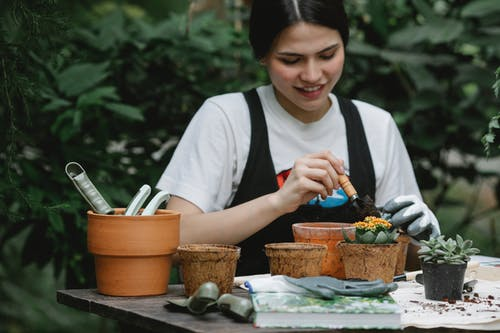 Smiling woman planting flower in pot