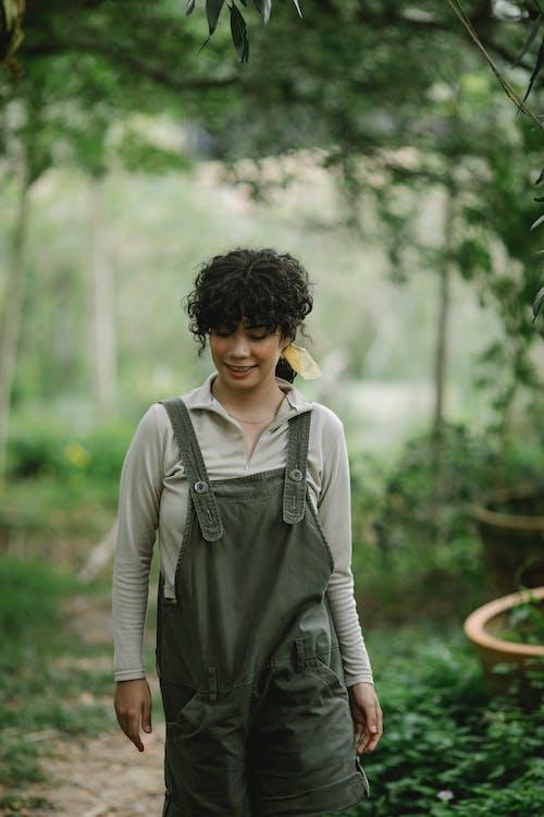 Smiling gardener standing in green garden