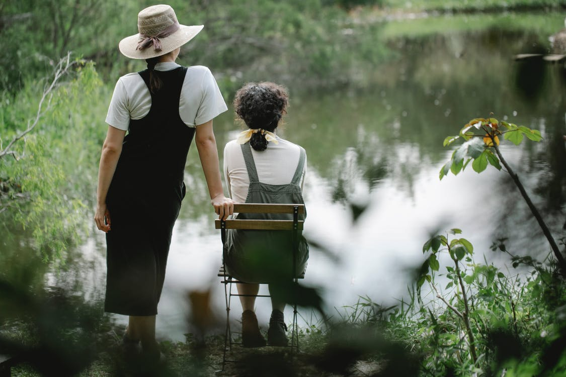 Back view full body of unrecognizable female gardeners enjoying view of lake in rural area