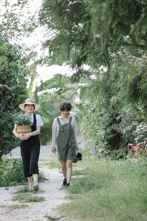 Uomo E Donna Che Tengono Le Mani Mentre Si Cammina Sul Campo Di Erba Verde
