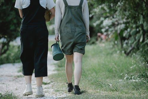 Female gardeners strolling on path in park