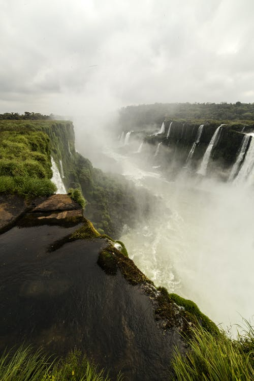 Amazing waterfall flowing through rocky cliffs on overcast day