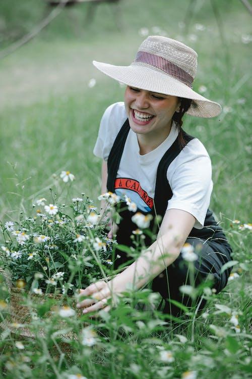 Joyful woman picking flowers in wicker basket