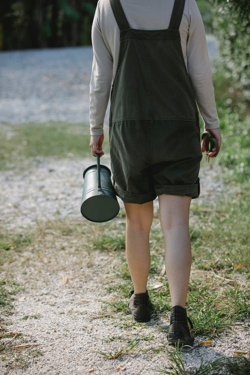 Back view of anonymous female gardener walking on pathway with watering can in farm