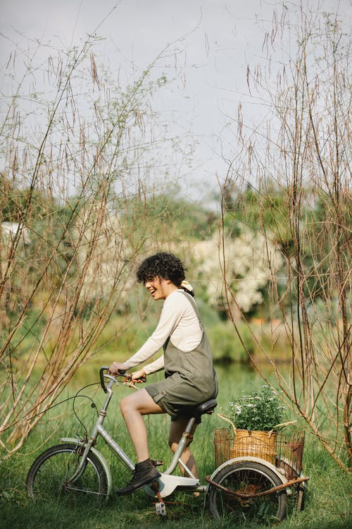 Full body side view of positive female on bike with plants in basket on coast of lake in countryside
