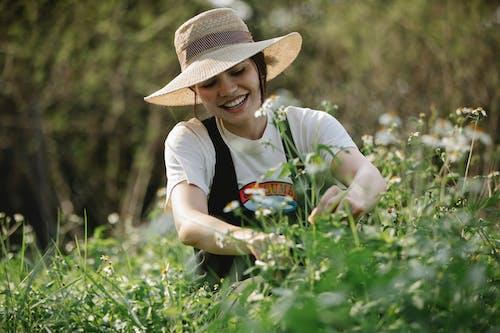 Donna In Maglietta Bianca E Cappello Marrone Che Si Siede Sull'erba Verde