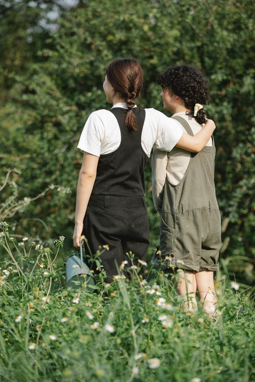 Unrecognizable female friends standing in grassy field with watering can