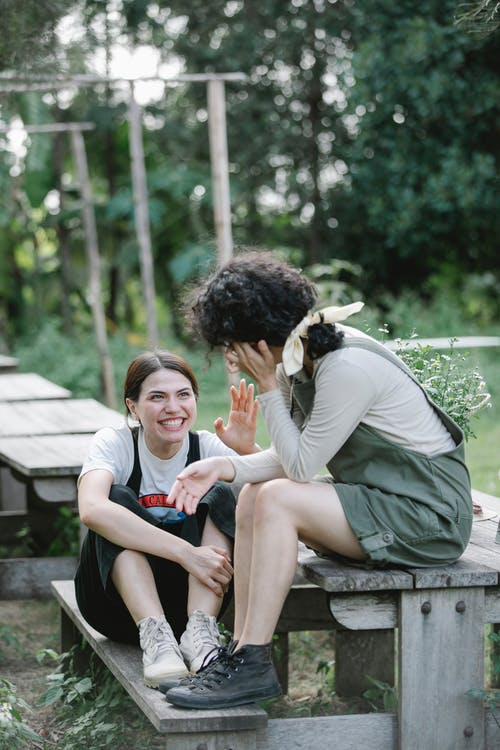 Full length of smiling young women in overalls having conversation while sitting on wooden bench in camp near green trees and grass with plants and looking at each other