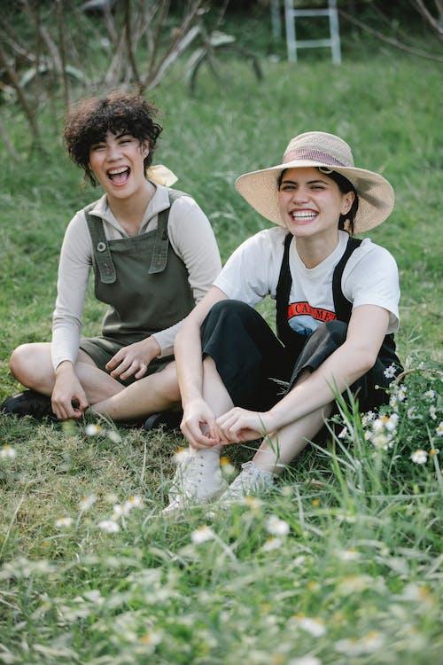 Happy multiethnic female friends sitting on green field in countryside