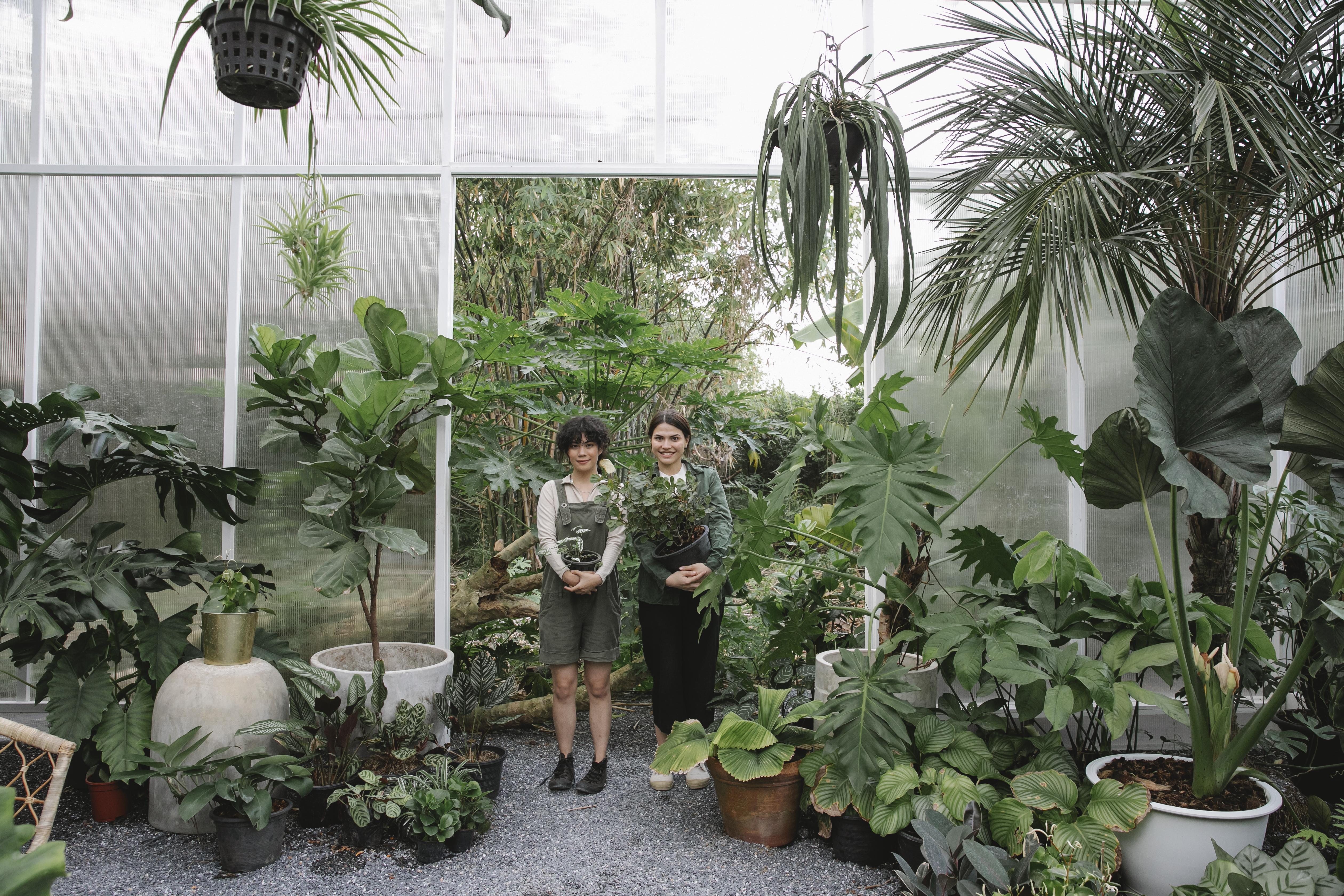 ethnic female gardeners with flowerpots
