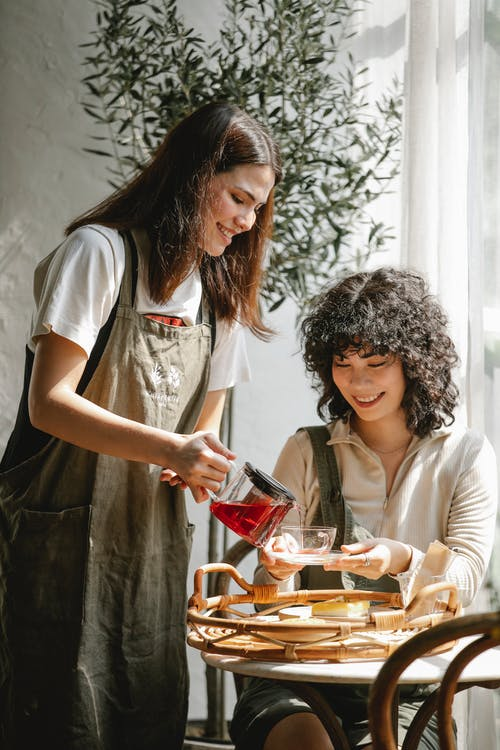 Cheerful ethnic coworkers with teapot at table