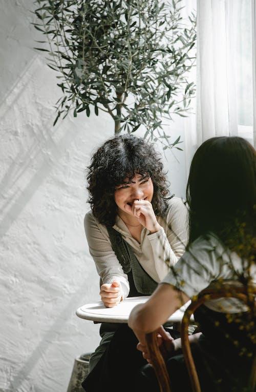 Mujer En Camisa De Manga Larga Gris Sentada En Una Silla