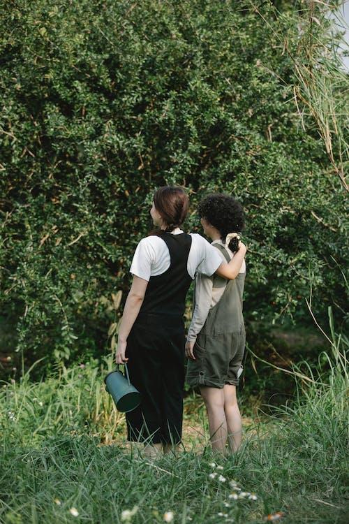 Unrecognizable gardeners on green meadow