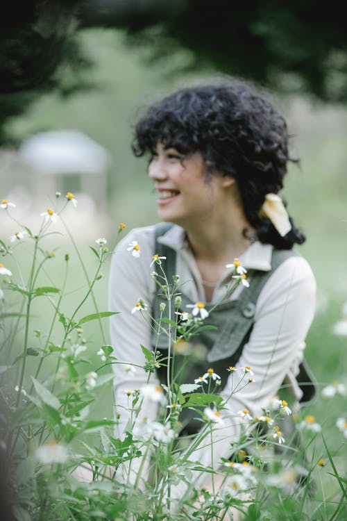 Smiling ethnic woman sitting near flowers