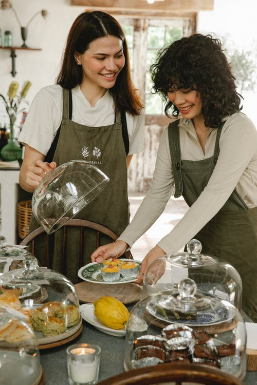Positive female colleagues wearing aprons standing at table with glass dome lids and various desserts while working in modern cafeteria