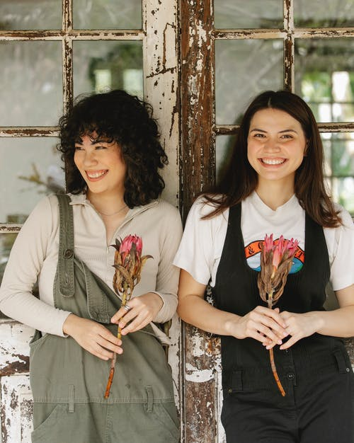 Smiling ethnic women with flowers near weathered door