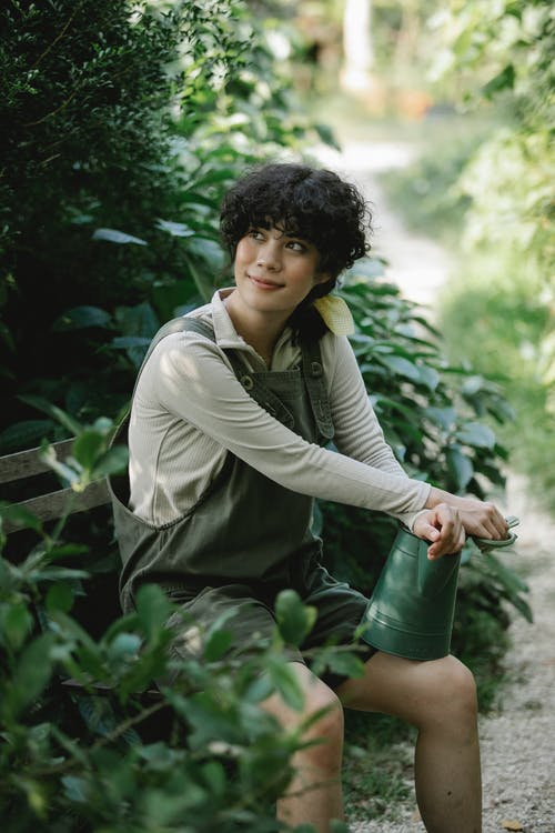 Cheerful ethnic female gardener looking away while sitting with metal watering can near green bush in botanical garden with pond on blurred background