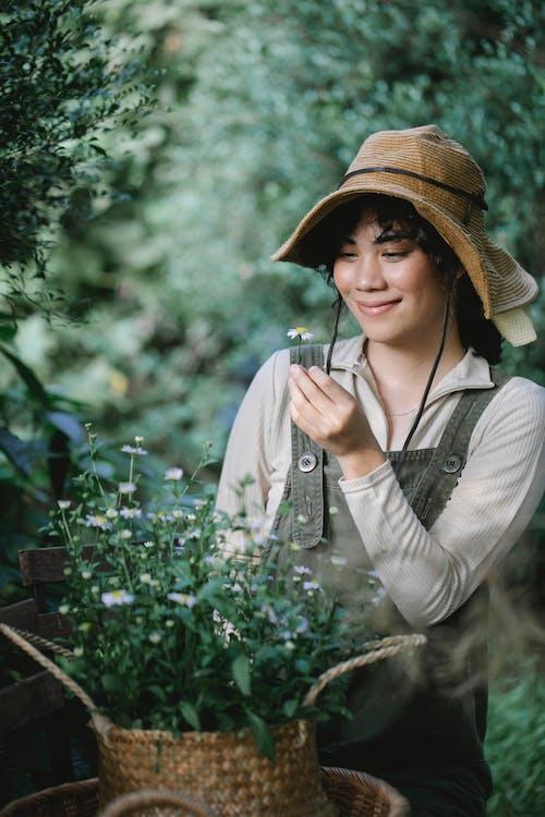 Happy ethnic woman basket of chamomiles