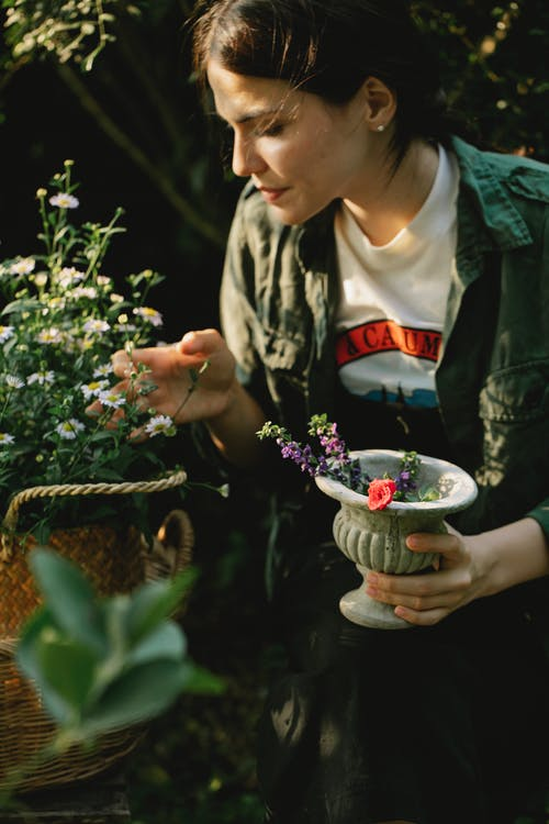 Side view of concentrated female gardener with pot of colorful flowers standing near wicker basket with small blooming flowers on green stems