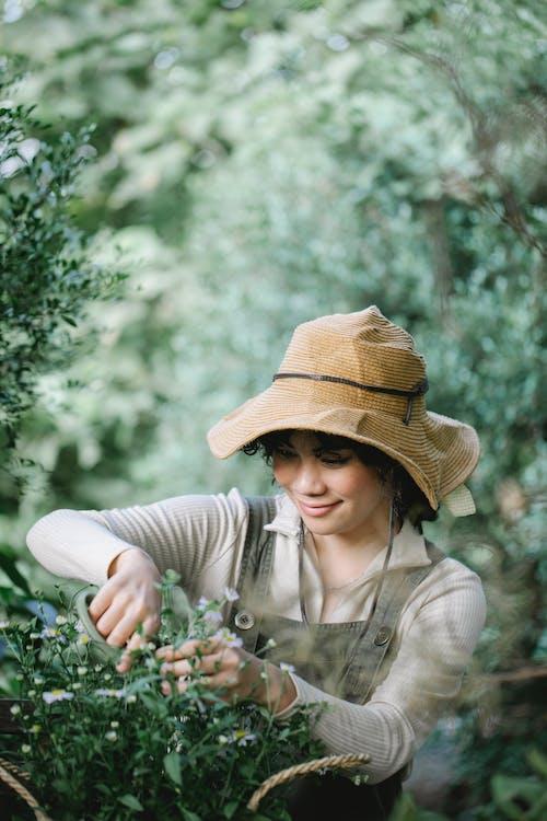 白い花を保持している茶色の麦わら帽子を身に着けている灰色の長袖シャツの女性