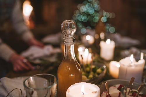 Selective Focus Photography of Clear Glass Bottle With White Candle