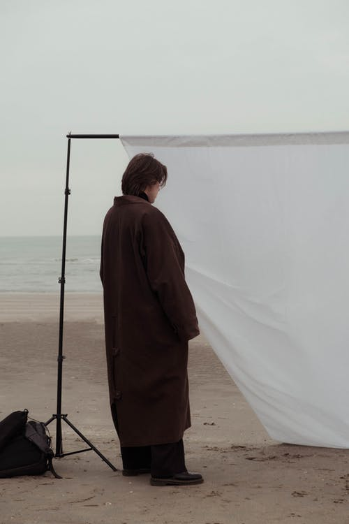 Back view of anonymous model in long stylish coat standing near white fabric sheet on stand placed on sandy shore of ocean in cloudy day