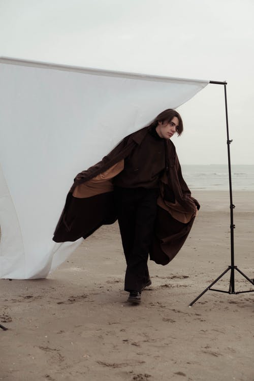 Man stylish clothes standing near fabric background placed on beach