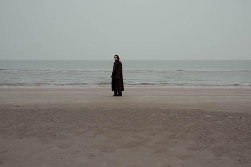Stylish man standing on coast near sea